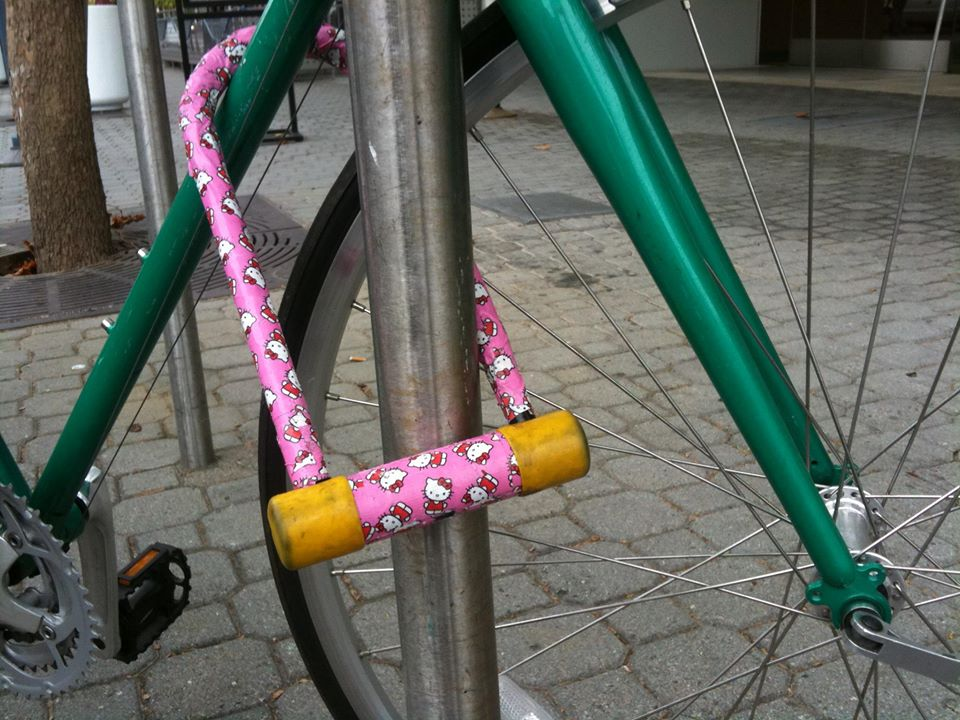 photo of a bicycle secured to a rack using a pink Hello Kitty U-lock