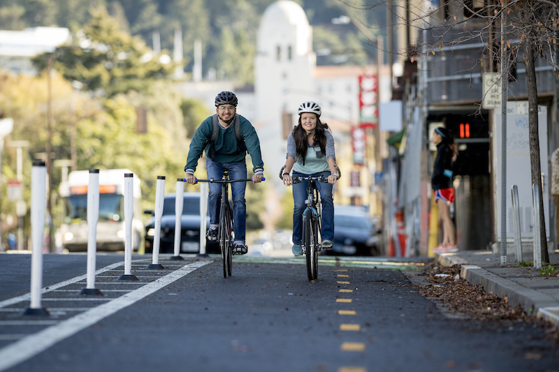 UC Berkeley junior Sebastian Gonzalez and senior Megan Bradley ride the Bancroft Way protected bike lane.