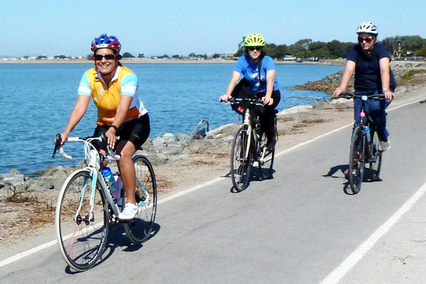 Image: Three smiling bicyclists ride the Bay Trail.